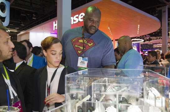 Former NBA star Shaquille O'Neal looks over smart watches powered with Qualcomm technology at the Qualcomm booth during the 2015 International Consumer Electronics Show (CES) in Las Vegas