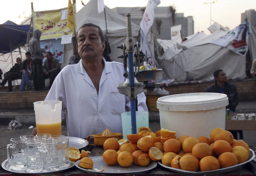"A vendor sells orange juice at his pushcart named ""Revolution Juice"" at Tahrir Square in Cairo"
