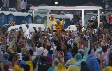 A pilgrim raises a statue of baby Jesus in front of Pope Francis after a Mass at Rizal Park in Manila