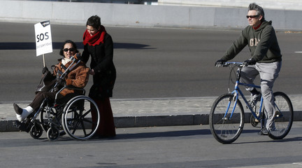 """A woman in a wheelchair carries a sign which reads, """"SOS disability"""" during a rally against government cutbacks for disabled people in Madrid"""