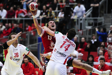 Serbia's Ilic attempts to score next to Denmark's Nielsen and Knudsen during their Men's European Handball Championship group B match in Linz