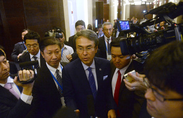 Japan's Minister in charge of TPP Ishihara (C) is mobbed by reporters as leaves after TPP11 in Hanoi