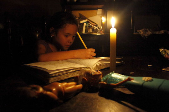 A girl does her homework by candlelight at his home during a power cut in San Cristobal