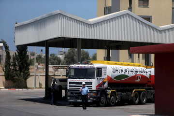 A worker speaks on the phone as a fuel tanker arrives at Gaza's power plant in the central Gaza Strip