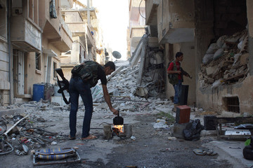 A Free Syrian Army fighter makes tea as a fellow fighter looks inside a building in Deir al-Zor