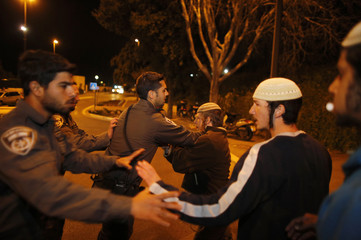 Israeli border police officers scuffle with Jewish settlers taking part in a protest outside the Knesset, in Jerusalem
