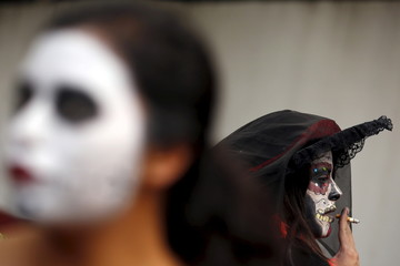 "A woman with her face painted to look like the popular Mexican figure called ""Catrina"", smokes a cigarette as she takes part in the annual Catrina Fest in Mexico City"