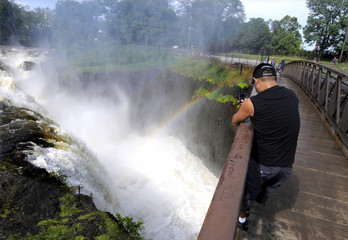 A man takes a photo of a rainbow at the water falls on the Passaic River in Paterson