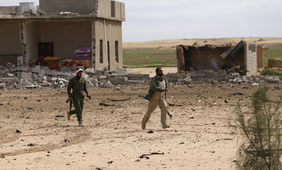 Shi'ite fighters carry their weapons as they run past the buildings used by the Islamic state militants on the outskirts of al-Alam