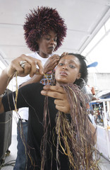 A woman gets her hair braided with raffia, a natural fibre drawn from a palm tree, walk during a fashion show organized by Ivorian designer Genevieve Koukougnon, in Abidjan