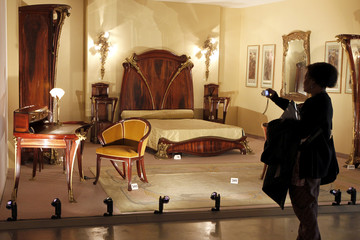 A visitor pictures bedroom pieces by French furniture designer Louis Majorelle part of the Chateau de Gourdon collection, are presented at the Palais de Tokyo in Paris