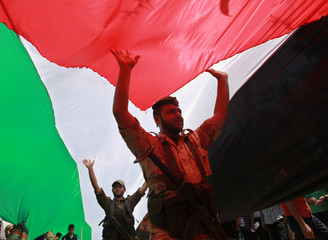 Members of Hamas security forces carry a large Palestinian flag during a rally marking Nakba in Gaza City