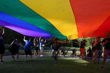 People run under a giant rainbow flag during a vigil for the Pulse night club victims following last weeks shooting in Orlando