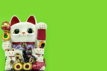 Lucky cat (Maneki Neko) on green background with copy space. Common Japanese sculpture bring good luck to the owner.