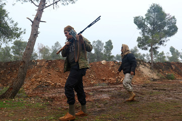 Rebel fighters walk with their weapons at insurgent-held al-Rashideen