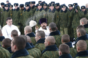 An Orthodox priest blesses servicemen of the Belarussian Interior Ministry's special force during a service to celebrate Orthodox Christmas at a military base in Minsk