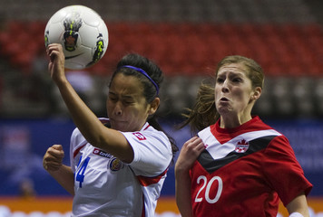 Costa Rica's Ugalde and Canada's Buckland react to the ball during the CONCACAF women's Olympic qualifying soccer match in Vancouver