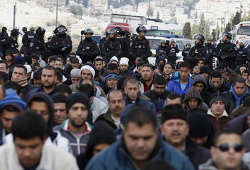 Palestinians pray as Israeli policemen guard during Friday prayers in the Arab east Jerusalem neighbourhood of Ras al-Amud