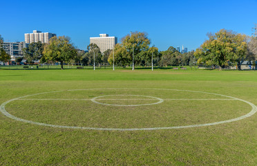 The center circle of a suburban AFL foobal ground with the goal posts and city skyline in the background.