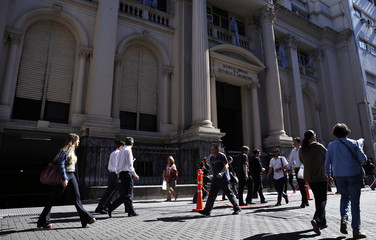 People walk past Argentina's Central Bank in Buenos Aires' financial district