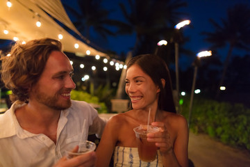 Fotobehang - Couple dating drinking at bar on night out at outdoor restaurant terrace in Hawaii vacation travel. Asian woman, man having fun together toasting mai tai drinks, hawaiian cocktail. Luxury lifestyle.