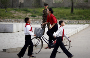 A soldier looks on near local residents walking and cycling at a street in Rajin at the Special Economic Zone of Rason City