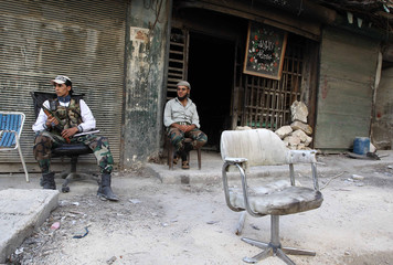 Members of the Free Syrian Army sit as one of them holds a weapon in Aleppo's Karm al-Jabal district