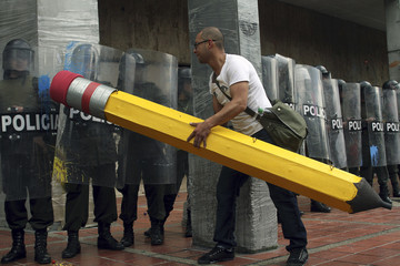 A student holding a pencil tries to 'erase' riot police during a demonstration in Bogota