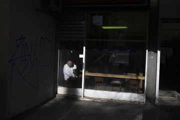 A barber sits inside his shop as he waits for customers in Athens