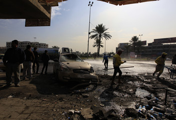 People gather at the site of car bomb attack in Baghdad