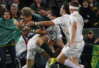 South Africa's captain De Villiers breaks past England's defenders to score a try during their first rugby test match in Durban