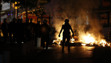 Riot police walk past a burning barricade during clashes with anti-government protesters in Ankara