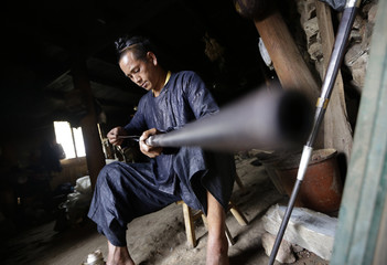 Ethnic Miao man Gun Yuangu uses a twig and engine oil to lubricate a gun at his house in the village of Basha in Congjiang county