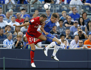 Chelsea's Sam Hutchinson and Paris St Germain's Sylvain Armand battle for a ball in the first half of their team's friendly soccer match at Yankee Stadium, the home of the New York Yankees baseball team, in New York