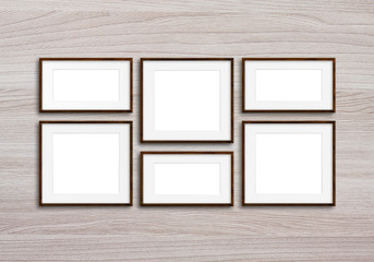 Six brown photo frames set on wooden panels wall
