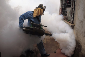 A health worker fumigates against mosquitoes inside home in Managua