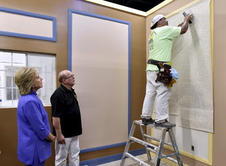 Democratic U.S. presidential candidate Hillary Clinton looks on as instructor Marvin Alexander watches over union apprentice Luis Rodriguez hang wallpaper during a visit to the IUPAT training center in Las Vegas, Nevada
