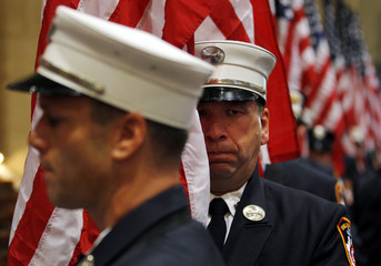 New York firefighters carry U.S. flags into the 9/11 firefighter's memorial service at St. Patrick's Cathedral in New York