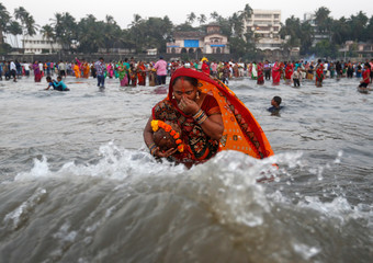 A Hindu devotee takes a dip as she worships the Sun god in the waters of the Arabian Sea during Chhath Puja in Mumbai
