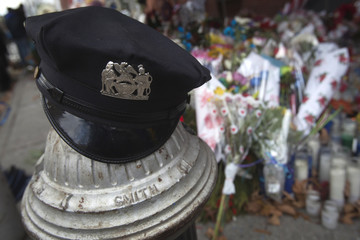 A police hat is pictured at a makeshift memorial for two NYPD officers who were fatally shot, in the Brooklyn borough of New York