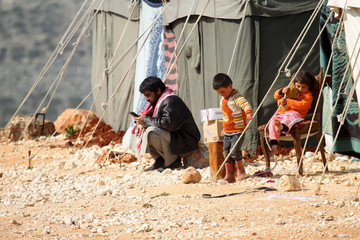 An internally displaced Syrian family that fled from Aleppo rests near tents in the village of Batabo, northern Idlib countryside