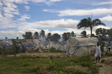 Haitians stand outside their tents in a camp for people affected by the 2010 earthquake, outside of Port-au-Prince