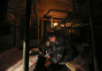 A woman sits in a basement used as a shelter from artillery fire in Donetsk