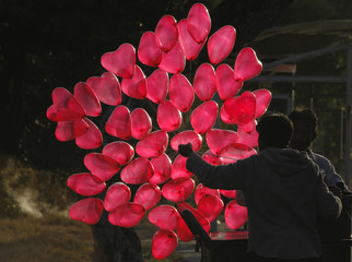 A man is silhouetted as he fills heart shaped balloons with helium while waiting for customers on Valentine's Day in Islamabad
