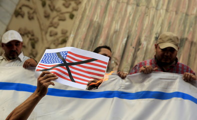 An activist shouts slogans against the U.S. with a burning picture of their flag during a protest in front of the Syndicate of Journalists in Cairo