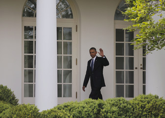U.S. President Barack Obama waves after arriving back at the White House in Washington