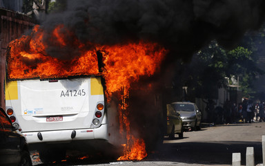 A burning bus set on fire by residents of the Telerj slum is seen as police attempt to repossess the land in Rio de Janeiro