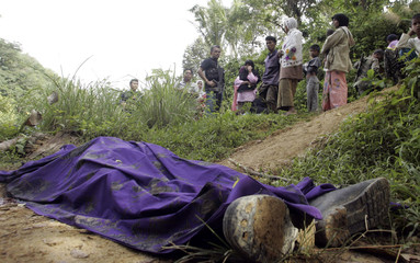 Thai security personnel inspect the body of a rubber tapper at a plantation in southern Thailand's Yala province