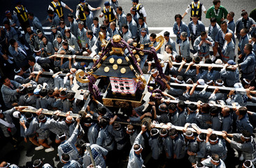 People carry a portable shrine, a Mikoshi, near the Senso-ji Temple during the Sanja festival in Asakusa district in Tokyo