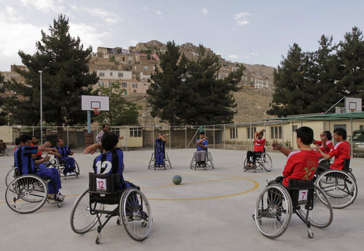 Disabled Afghans exercise on their wheelchairs on a basketball court in Kabul